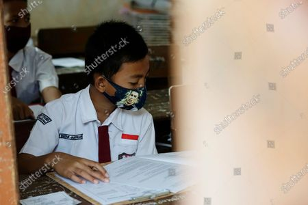 Stock Image of An elementary school student in Palembang is taking a junior high school entrance test wearing a character mask with a picture of Cristiano Ronaldo and carrying a hand sanitizer.