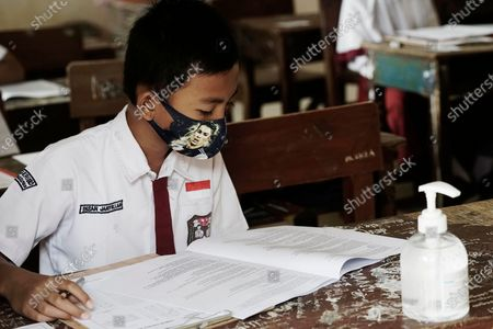 Stock Picture of An elementary school student in Palembang is taking a junior high school entrance test wearing a character mask with a picture of Cristiano Ronaldo and carrying a hand sanitizer.