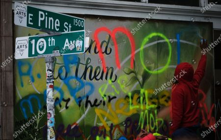 A mourner spray paints a memorial to man killed outside the 'Occupied Zone' in the Capitol Hill neighborhood near a police station, abandoned by police, in Seattle, Washington, USA, 20 June 2020. For several weeks activists have occupied part of the Capitol Hill neighborhood to protest police brutality and support the Black Lives Matters movement. While the occupation has been relatively peaceful, a man was shot and killed just outside of the zone early in the morning of 20 June.
