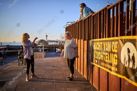 Dutch Minister of Foreign Trade and Development Cooperation Sigrid Kaag (L) and Director of the Refugee Foundation Andrew Makkinga Tineke Ceelen (R) chat with passersby during a digital edition of the Night of the Refugee in Scheveningen, The Netherlands, 20 June 2020 (issued 21 June 2020). Due to coronavirus prevention measures, the 11th edition of the annual event differed from previous years. This year, runners did not leave from a central point, but instead walked in their own environment.