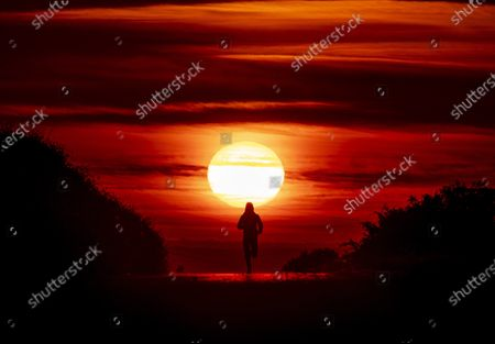 Woman runs on a small road betweenfileds and acres as the sun rises in Frankfurt, Germany