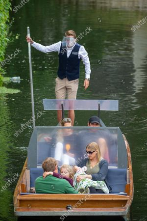 """New style punt being tested for the first time on the River Cam in Cambridge .The punt has been fitted with perspex screens  to help with social distancing between different households. Traditional punts in Cambridge have been fitted with PERSPEX screens to help with social distancing between different households.Punts have looked the same for the last 120 years, but now Lets Go Punting and The Traditional Punting Company have given their boats a makeover so they can safely re-open.The companies, which plan to re-launch on Saturday, July 4, have fixed Perspex screens to their boats to ensure there is a protective barrier between different groups of people when the current two metre minimum distance is not met.Joe Merwiak, owner of The Traditional Punting Company, said: """"The punting companies have been working hard over the lockdown period to ensure the safe return of punting, so everyone can enjoy the College Backs of Cambridge. """"While punting may look slightly different for a while, it will still be a beautiful and relaxing experience.""""n covers and will implement a strict cleaning procedure between tours. People must now book their punts online and there is a new text message service to help notify customers of their departure so they can avoid having to queue for a tour."""