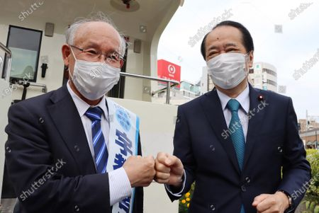Former president of Japan Federation of Bar Associations Kenji Utsunomiya (L) exchanges a fist bump with former Prime Minister Naoto Kan (R) ypon his arrival as he delivers a campaign speech for the Tokyo gubernatorial election campaign in Tokyo on Saturday, June 20, 2020. Official campaign for the July 5 Tokyo gubernatorial election with 22 candidates including Tokyo Governor Yuriko Koike started on June 18.