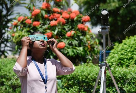 A girl view the annular solar eclipse using special filters, in Guwahati, Assam, India on Sunday, June 21, 2020.
