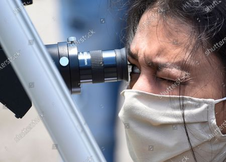 A girl looks through a telescope to get a glimpse of Solar Eclipse, at Guwahati Planetarium in Guwahati, Assam, India on Sunday, June 21, 2020.