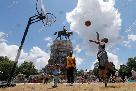 Isaiah Bowen, right, takes a shot as his dad, Garth Bowen, center, looks on at a basketball hoop in front of the statue of Confederate General Robert E. Lee on Monument Avenue, in Richmond, Va. A judge extended an injunction delaying the removal of the statue by the state. The statue had become a focal point for the Black Lives Matter movement in Richmond