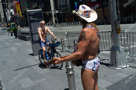 Robert Burck, better known as The Naked Cowboy, plays guitar in Times Square. New Yorkers will be able to go back to hair salons, dine outdoors and shop in-stores as Phase 2 of reopening launches on June 22.