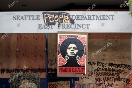 1970's-era poster of activist Angela Davis hangs at a boarded up and closed Seattle police precinct, in Seattle, where streets are blocked off in what has been named the Capitol Hill Occupied Protest zone. Police pulled back from several blocks of the city's Capitol Hill neighborhood near the Police Department's East Precinct building earlier in the month after clashes with people protesting the death of George Floyd, a Black man who died after being restrained by Minneapolis police officers on May 25