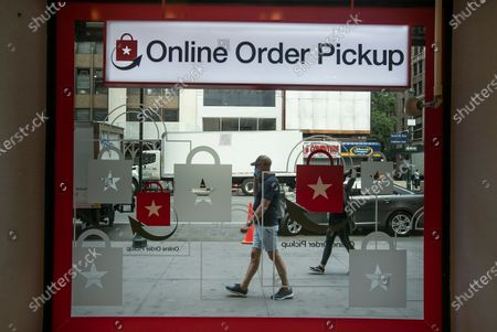 Pedestrians pass the online order pickup area at the Macy's Herald Square location, in New York. New York City hits a key point Monday in trying to rebound from the nation's deadliest coronavirus outbreak. For the first time in three months, New Yorkers will be able to dine out, though only at outdoor tables. Shoppers can once again browse in the city's destination stores. Shaggy heads can get haircuts. Cooped-up kids can finally climb playground monkey bars instead of apartment walls. Office workers can return to their desks, though many won't yet