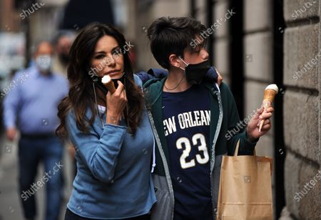Stock Picture of Emanuela Folliero and her son Andrea stroll through the streets of the center while eating an ice cream cone. Here they are together walking in via Montenapoleone.