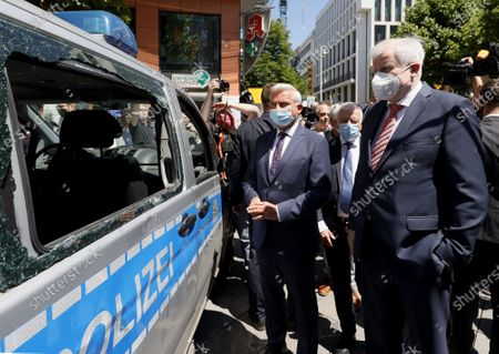 German Interior Minister Horst Seehofer (R) stands next to Baden-Wuerttemberg's Interior Minister Thomas Strobl (C) looking at a damaged police car during a visit to the downtown shopping area in Stuttgart, 22 June 2020. Several hundreds of rioting youths vandalized and looted dozens of shops in the center of Stuttgart, the capital of the federal state of Baden-Wuerttemberg, in the early morning of 21 June 2020, reports state. The rioters also hurled rocks at police officers until the situation calmed down around 3 am. Authorities have yet to provide an explanation about what exactly sparked the unrest.