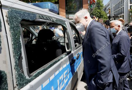 German Interior Minister Horst Seehofer (L) stands next to Baden-Wuerttemberg's Interior Minister Thomas Strobl (C) looking at a damaged police car during a visit to the downtown shopping area in Stuttgart, 22 June 2020. Several hundreds of rioting youths vandalized and looted dozens of shops in the center of Stuttgart, the capital of the federal state of Baden-Wuerttemberg, in the early morning of 21 June 2020, reports state. The rioters also hurled rocks at police officers until the situation calmed down around 3 am. Authorities have yet to provide an explanation about what exactly sparked the unrest.