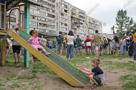 A baby girl goes down a slide at a playground as onlookers watch the response effort to the explosion in a nine-storey building in the Darnytskyi district of Kyiv, capital of Ukraine. An explosion went off on Sunday morning, June 21, killing three people. Another three people are missing while 100 residents will have to leave their homes. The investigation is ongoing.