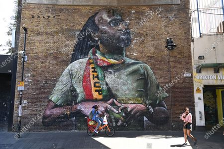 People walk past a giant artwork in Brixton in London, Britain, 22 June 2020. The day marks the third Windrush Day and is the 72nd anniversary of the SS Empire Windrush arriving at Tilbury Docks in Essex carrying the first Caribbean migrants bringing workers from Jamaica, Trinidad and Tobago and other islands, as a response to post-war labour shortages in the UK. Brixton was the first 'Windrush community' in 1948 and it is still it is a vibrant centre for Caribbean culture with the Windrush Square standing in the centre of Brixton.