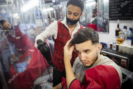 David Fernandez receives his first haircut in four months at Ace of Cuts barbershop, in New York. For the first time in three months, New Yorkers will be able to dine out, though only at outdoor tables. Shoppers can once again browse in the city's destination stores. Shaggy heads can get haircuts. Cooped-up kids can finally climb playground monkey bars instead of apartment walls. Office workers can return to their desks, though many won't yet