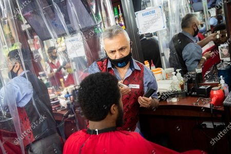 Sam Shamuelov, wears a protective mask as he gives a haircut to a customer at Ace of Cuts barbershop, in New York. For the first time in three months, New Yorkers will be able to dine out, though only at outdoor tables. Shoppers can once again browse in the city's destination stores. Shaggy heads can get haircuts. Cooped-up kids can finally climb playground monkey bars instead of apartment walls. Office workers can return to their desks, though many won't yet