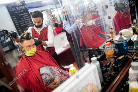Brian Nieh wears a protective mask as he receives a haircut at Ace of Cuts barbershop, in the Manhattan borough of New York. For the first time in three months, New Yorkers will be able to dine out, though only at outdoor tables. Shoppers can once again browse in the city's destination stores. Shaggy heads can get haircuts. Cooped-up kids can finally climb playground monkey bars instead of apartment walls. Office workers can return to their desks, though many won't yet