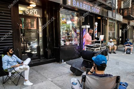 Customers wait on the sidewalk before receiving haircuts while a DJ plays outside Ace of Cuts barbershop, in New York. For the first time in three months, New Yorkers will be able to dine out, though only at outdoor tables. Shoppers can once again browse in the city's destination stores. Shaggy heads can get haircuts. Cooped-up kids can finally climb playground monkey bars instead of apartment walls. Office workers can return to their desks, though many won't yet