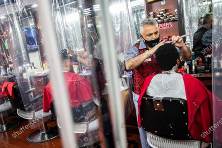 Sam Shamuelov wears a protective mask as he gives a haircut to a customer at Ace of Cuts barbershop, in New York. For the first time in three months, New Yorkers will be able to dine out, though only at outdoor tables. Shoppers can once again browse in the city's destination stores. Shaggy heads can get haircuts. Cooped-up kids can finally climb playground monkey bars instead of apartment walls. Office workers can return to their desks, though many won't yet
