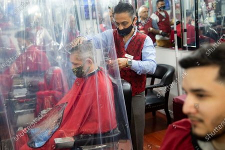 Peter Shamuelov, center, wears a protective mask as he gives a haircut to a customer at Ace of Cuts barbershop, in New York. For the first time in three months, New Yorkers will be able to dine out, though only at outdoor tables. Shoppers can once again browse in the city's destination stores. Shaggy heads can get haircuts. Cooped-up kids can finally climb playground monkey bars instead of apartment walls. Office workers can return to their desks, though many won't yet