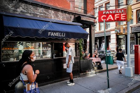 Customers dine outside Fanelli's Cafe as to-go orders are picked up at a curbside window, in New York. For the first time in three months, New Yorkers will be able to dine out, though only at outdoor tables. Shoppers can once again browse in the city's destination stores. Shaggy heads can get haircuts. Cooped-up kids can finally climb playground monkey bars instead of apartment walls. Office workers can return to their desks, though many won't yet