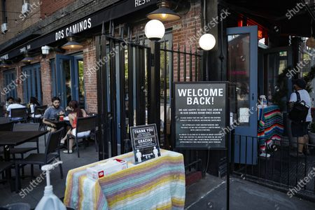 Customers dine outside Dos Caminos, in New York. For the first time in three months, New Yorkers will be able to dine out, though only at outdoor tables. Shoppers can once again browse in the city's destination stores. Shaggy heads can get haircuts. Cooped-up kids can finally climb playground monkey bars instead of apartment walls. Office workers can return to their desks, though many won't yet