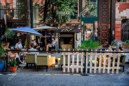 Customers dine outside PhoBar, in New York. For the first time in three months, New Yorkers will be able to dine out, though only at outdoor tables. Shoppers can once again browse in the city's destination stores. Shaggy heads can get haircuts. Cooped-up kids can finally climb playground monkey bars instead of apartment walls. Office workers can return to their desks, though many won't yet