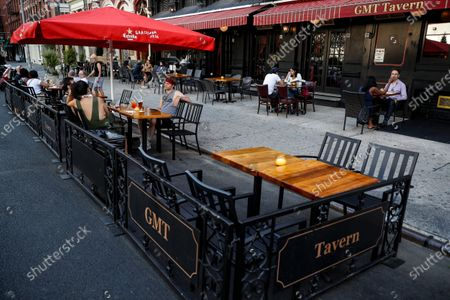Stock Picture of Customers dine outside GMT Tavern, in New York. For the first time in three months, New Yorkers will be able to dine out, though only at outdoor tables. Shoppers can once again browse in the city's destination stores. Shaggy heads can get haircuts. Cooped-up children can finally climb playground monkey bars instead of apartment walls. Office workers can return to their desks, though many won't yet