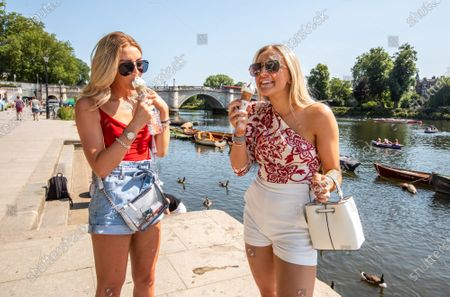 Sophie Taylor and Neve Foster both 18 enjoy an ice cream in the sunshine along the Richmond Riverside in South West London as forecasters predict a hot week ahead with temperatures expected to reach over 30c. Prime Minister, Boris Johnson announces that tourism and hospitality including pubs, restaurants and campsites can now reopen from the 4th of July as well as reducing the 2 metre rule to 1 metre. Photo credit: Alex Lentati/LNP   *Permission Given*