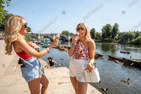 Stock Photo of Sophie Taylor and Neve Foster both 18 enjoy an ice cream in the sunshine along the Richmond Riverside in South West London as forecasters predict a hot week ahead with temperatures expected to reach over 30c. Prime Minister, Boris Johnson announces that tourism and hospitality including pubs, restaurants and campsites can now reopen from the 4th of July as well as reducing the 2 metre rule to 1 metre. Photo credit: Alex Lentati/LNP   *Permission Given*