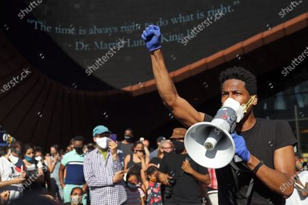 Stock Image of Jon Batiste leads a Black Lives Matter rally outside the Barclays Center in Brooklyn NY on June 12, 2020. Batiste, the band leader for the Late Show with Stephen Colbert, sang, played the piano and the melodica at the event.