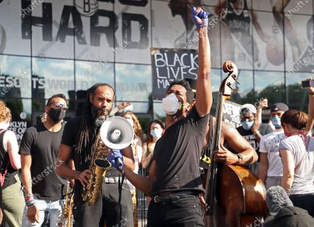 Stock Picture of Jon Batiste leads a Black Lives Matter rally outside the Barclays Center in Brooklyn NY on June 12, 2020. Batiste, the band leader for the Late Show with Stephen Colbert, sang, played the piano and the melodica at the event.