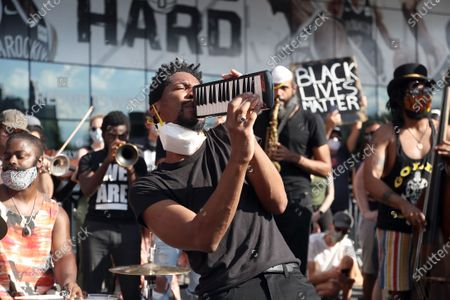 Jon Batiste leads a Black Lives Matter rally outside the Barclays Center in Brooklyn NY on June 12, 2020. Batiste, the band leader for the Late Show with Stephen Colbert, sang, played the piano and the melodica at the event.