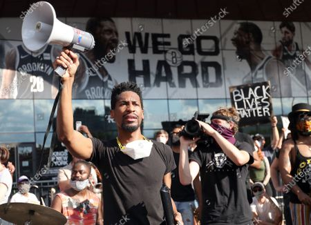 Stock Photo of Jon Batiste leads a Black Lives Matter rally outside the Barclays Center in Brooklyn NY on June 12, 2020. Batiste, the band leader for the Late Show with Stephen Colbert, sang, played the piano and the melodica at the event.