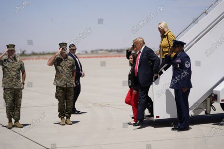 President Donald Trump departs from Air Force One with Sen. Martha McSally, R-Ariz., fourth from right, and Rep. Debbie Lesko, R-Ariz., second from right, at Marine Corps Air Station Yuma, Ariz