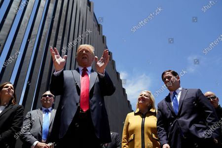 President Donald Trump speaks as he tours a section of the border wall, in San Luis, Ariz. Arizona Gov. Doug Ducey, second from right, and Rep. Debbie Lesko, R-Ariz., third from right