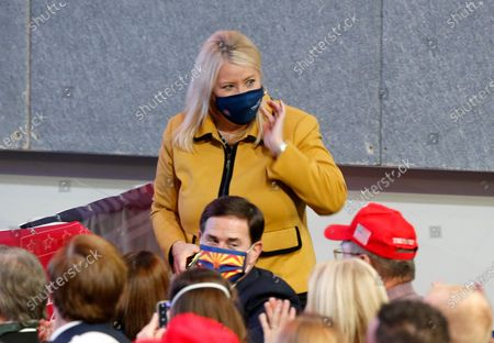 Both wearing masks Rep. Debbie Lesko, R-Ariz., and Republican Gov. Doug Ducey, bottom, talk to others prior to President Donald Trump speaking at the Students for Trump conference at Dream City Church, in Phoenix