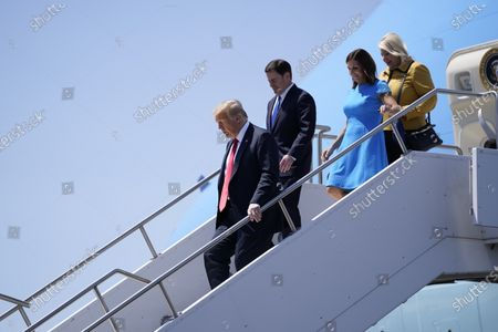 President Donald Trump exits Air Force One as he arrives at Phoenix Sky Harbor International Airport, in Phoenix. From left, Trump, Arizona Gov. Doug Ducey, Sen. Martha McSally, R-Ariz., and Rep. Debbie Lesko, R-Ariz