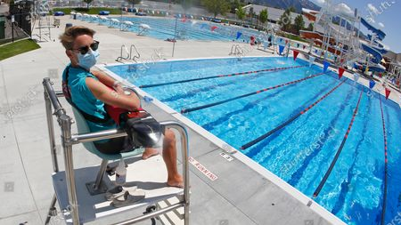 A life guard wears his mask as he sits on the chair while scanning the water at the Cottonwood Heights Recreation Center, in Cottonwood Heights, Utah. Gov. Gary Herbert tweeted, night that he appreciated the analysis by epidemiologist Angela Dunn that outlined the severity of the surge in COVID-19, but made clear he's not considering going backwards with a plan he rolled out in early May that gradually allowed businesses, gyms, salons and pools to reopen