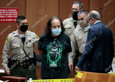 Adult film star Ron Jeremy, second left, with his attorney Stuart Goldfarb, right, makes his first appearance in Dept. 30 at Los Angeles Superior Court in Los Angeles, . Los Angeles County prosecutors say Jeremy has been charged with raping three women and sexually assaulting a fourth