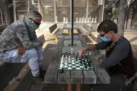 Wearing face coverings, John Williams, right, and Jeff Lee play chess, in Santa Monica, Calif. The state Department of Public Health recorded more than 5,000 new cases Tuesday, putting the total number of positive cases at more than 183,000. The state has seen more than 5,500 deaths related to COVID-19