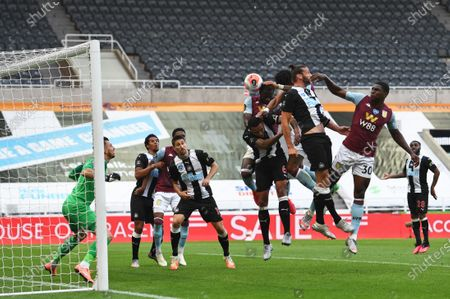 Kortney Hause of Aston Villa beats /Andy Carroll of Newcastle United to the ball