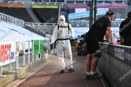 Stock Image of A member of staff sterilises the pathway during half time at St. James' Park