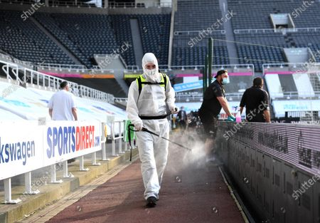 A member of staff sterilises the pathway during half time at St. James' Park