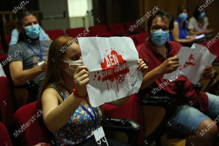 """Members of the court audience wear protective masks and hold up banners that read """" Nazis are not innocent"""" during the first day of the restart after the curfew of the trial of the Golden Dawn (Chrysi Avgi) party, in Athens, Greece, 24 June 2020. The trial is on its final stage after six years of procedure."""