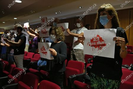 Members of the court audience wear protective masks and hold up banners that read 'Nazis are not innocent' during the first day of the restart after the curfew of the trial of the Golden Dawn (Chrysi Avgi) party, in Athens, Greece, 24 June 2020. The trial is on its final stage after six years of procedure.