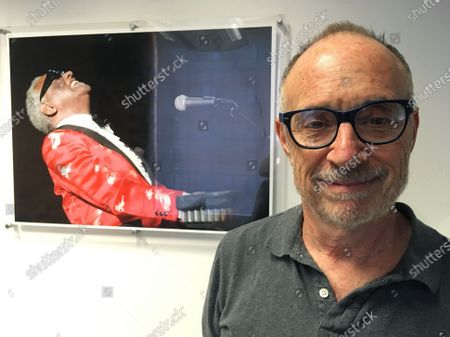 Stock Image of In this June 18, 2018 photo, Gregory Katz, acting London bureau chief for The Associated Press, poses for a photo backdropped by a photo of American pianist singer songwriter Ray Charles, at the AP's London office. Katz, an acclaimed correspondent for The AP whose career over four decades took him across the globe, died . He had been ill in recent months and had contracted COVID-19. He was 67
