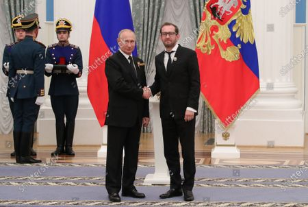 Stock Image of Russian President Vladimir Putin (C) shakes hands with Konstantin Khabensky (R), actor, film director and charity founder, during a ceremony to present Russian National Awards for outstanding achievements in science and technology, literature and the arts, humanitarian activity, charity work and human rights at the Kremlin in Moscow, Russia, 24 June 2020.
