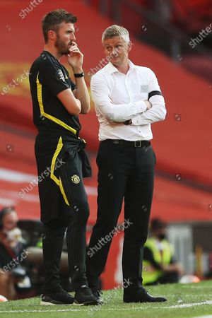 Manchester United manager Ole Gunnar Solskjaer (R) talks to assistant coach Michael Carrick during the English Premier League match between Manchester United and Sheffield United in Manchester, Britain, 24 June 2020.