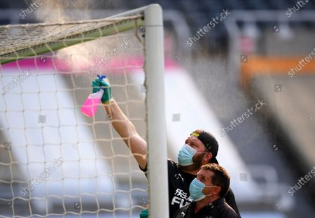 The crossbar of a goal is sprayed with disinfectant before the English Premier League match between Newcastle United and Aston Villa in Newcastle, Britain, 24 June 2020.